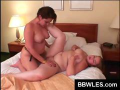 Fatty chicks have some lesbian lovin' fun with the aid of a strap-on