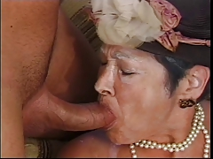 Older woman blows young dude's hard cock on couch